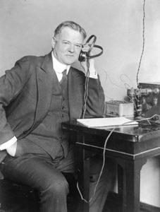 Herbert Hoover, three-quarter length portrait, seated, facing slightly right, listening to radio.